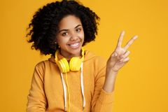 Handsome african american young woman with bright smile dressed in casual clothes and headphones showing peace gesture. Over yellow background stock photography