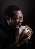 Handsome african black man eating ostrich egg. royalty free stock images