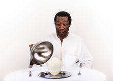 Handsome african black man with ostrich egg on his plate. Stock Photography