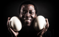 Handsome african black man with ostrich egg. Royalty Free Stock Photos