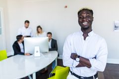 Handsome african businessman in front group of businesspeople on background royalty free stock photography