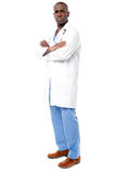 Handsome african doctor isolated on white. Confident male doctor standing with arms crossed Stock Photos