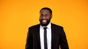 Handsome african male in formalwear smiling cheerfully to camera, ad template stock image