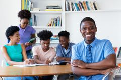 Handsome african male teacher with class at school. Handsome african male teacher with class at classroom of school stock photography
