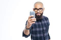 Handsome african man with beard taking selfie using smartphone. Handsome young hairless african young man with beard taking selfie using smartphone stock images