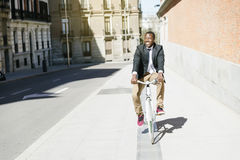 Handsome african man on bike in the city. Royalty Free Stock Photography