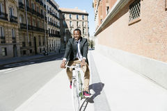 Handsome african man on bike in the city. Royalty Free Stock Photos