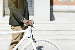 Handsome african man on bike in the city. Stock Photos