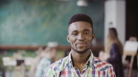 Handsome african man at busy modern office. Portrait of young successful male looking at camera and smiling. Stock Image