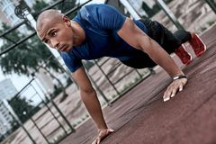 African man is doing plank at open air gym near the park stock image