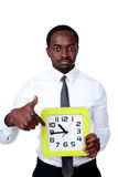 Handsome african man holding a clock Royalty Free Stock Photos