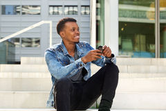 Handsome african man sitting on steps outside with mobile phone Stock Photos