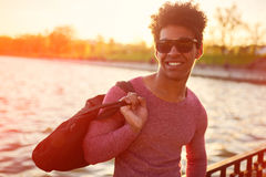 Handsome african man standing against a lake. Closeup of stylish handsome african man standing against a lake with sunlight effect. Fashion young male wearing Royalty Free Stock Images