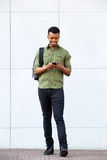Handsome african man standing with smart phone and bag. Full body portrait of handsome african man standing with smart phone and bag Royalty Free Stock Photos