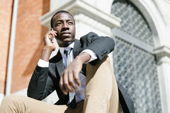 Handsome african man using his mobile. Royalty Free Stock Images