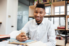 Handsome african student in library chatting by his phone. Stock Photos