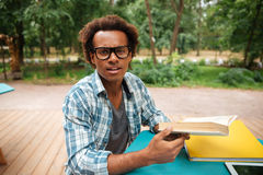 Handsome african young man reading and learning in outdoor cafe. Handsome african young man in glasses reading and learning in outdoor cafe Royalty Free Stock Image