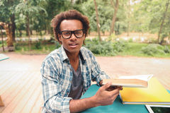 Handsome african young man reading and learning in outdoor cafe. Handsome african young man in glasses reading and learning in outdoor cafe Royalty Free Stock Photos