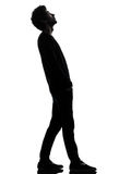 Handsome african young man standing looking up surprise silhouet. One african handsome young man standing looking up surprise   in silhouette studio isolated on Stock Images