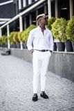 Handsome young Afro American business man wearing stylish clothes in modern city sits near the building stock images
