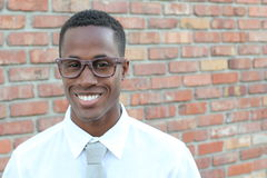 Handsome Afro American man in classic shirt, tie and glasses is looking at camera and smiling, against red brick wall, close up Royalty Free Stock Photos
