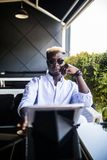 Handsome Afro American man is using a tablet, smiling while sitting on cafe terrace royalty free stock photography