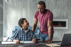 Father and son. Handsome Afro American men is watching his son drawing, both are smiling, at home royalty free stock photography