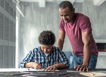 Father and son. Handsome Afro American men is smiling while watching his son drawing, at home royalty free stock photo
