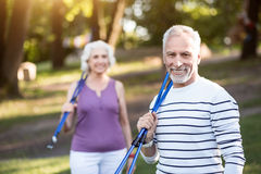 Handsome aged male smiling at the camera after nice work-out. Satisfied. Mature couple holding tracksticks while returning from the sport training in the woods Stock Photos