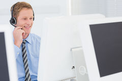 Handsome agent with headset typing on keyboard Royalty Free Stock Image