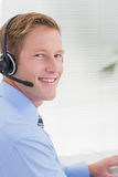 Handsome agent with headset typing on keyboard Royalty Free Stock Photography