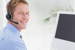Handsome agent with headset typing on keyboard Stock Images