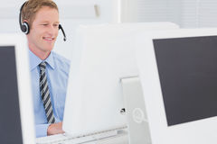 Handsome agent with headset typing on keyboard Stock Photos