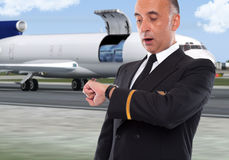 Handsome airline worker looking at his watch. With a cargo plane in the back Royalty Free Stock Images