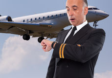 Handsome airline worker looking at his watch. Surprised Stock Photography