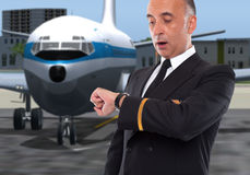 Handsome airline worker looking at his watch. Surprised Stock Photos