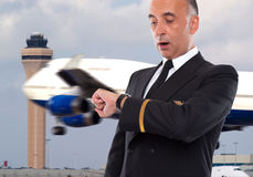 Handsome airline worker looking at his watch. With a surprised face Royalty Free Stock Image