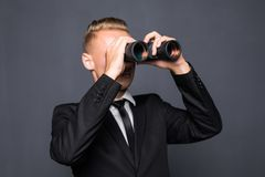 Handsome young american businessman using binoculars in office on gray background Stock Photo