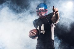 handsome american football player with ball pointing somewhere against stock photo