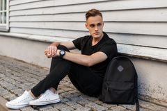 Handsome American man with a stylish hairstyle in a fashionable black T-shirt in stylish jeans in white sneakers with a backpack. Sits on the sidewalk near a royalty free stock images