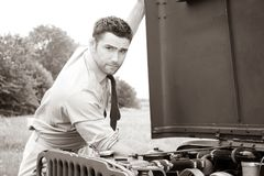 Handsome American WWII GI Army officer in uniform and rolled up sleeves next to broken down Willy Jeep royalty free stock photography