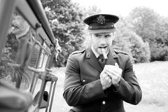 Handsome American WWII GI Army officer in uniform smoking cigar next to Willy Jeep. Vintage Handsome American man, Soldier, SGT in world war 2 officer`s uniform stock photo