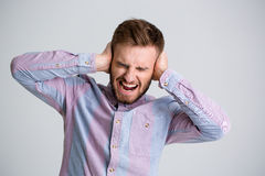Handsome angry bearded man closed ears by hands and shouting Stock Images