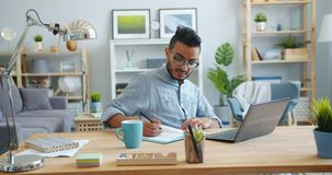 Handsome Arab working with laptop then writing in notebook at desk at home. Handsome young Arab freelancer is working with laptop then writing in notebook stock video footage