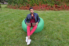 Handsome Arab Young Businessman Sits With Laptop in Chair, Looks. Attractive Young Arabic Guy, Businessman, Student Sits With Laptop in Soft Green Chair, Looks Royalty Free Stock Photos