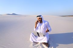 Handsome arabian guy businesswoman calling business partner sitt. Smart handsome emirate guy businessman prints on computer keyboard and answers incoming phone royalty free stock photography