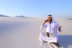 Handsome arabian guy businesswoman calling business partner sitt. Smart handsome emirate guy businessman prints on computer keyboard and answers incoming phone royalty free stock photos