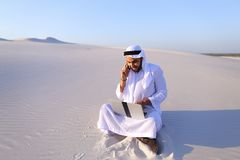 Handsome arabian guy businesswoman calling business partner sitt. Smart handsome emirate guy businessman prints on computer keyboard and answers incoming phone stock photos