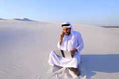 Handsome arabian guy businesswoman calling business partner sitt. Smart handsome emirate guy businessman prints on computer keyboard and answers incoming phone stock photo