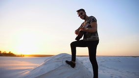 Handsome Arabian guy playing guitar, standing on hill among sandy desert at sunset in open air on warm evening. Romantic bearded young Arab man exercises stock video